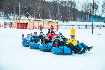 LVIV, UKRAINE - January 7, 2019: winter fun activities. ride down by hill on snow tubing. pushing