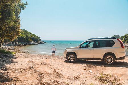car travel concept man at summer beach looking at sea freedom