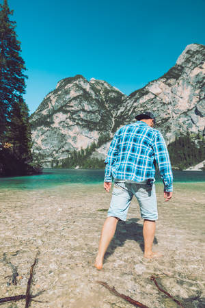 man walking by lake beach mountains on background summer time