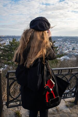 woman in black beret and winter coat taking picture of panoramic city view no face view from behind
