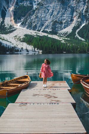 young beautiful woman in red dress walking by wooden pier at mountain lake. summer time