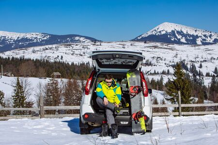 man sitting in car trunk changing for snowboard. mountains on background