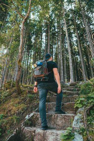 man with backpack walking by stone stairs that leads to the forest hiking concept