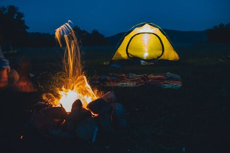 Langzeitbelichtung Lagerfeuer mit gelbem Zelt im Hintergrund. Platz kopieren Standard-Bild