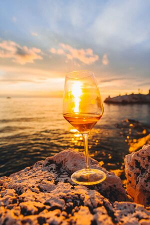 glass of wine at rocky sea beach on sunset. copy space. summer vacation Foto de archivo