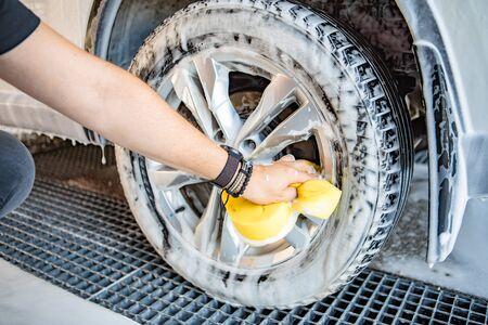 man hand holding yellow sponge cleaning car carwash Reklamní fotografie