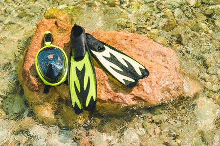 snorkeling mask with flippers at rock in sea water copy space