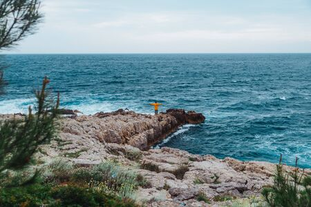 man walking by rock to storming sea. copy space