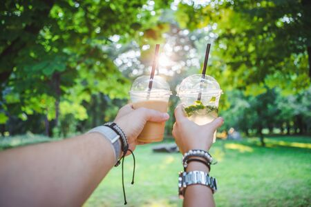 couple hands holding cup with cooling drink. walking by summer public park Imagens