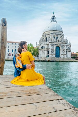couple hugging on pier with view of grand canal saint maria church on background. copy space