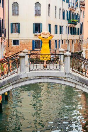woman in yellow sundress standing on the bridge cross venice canal summer vacation Фото со стока