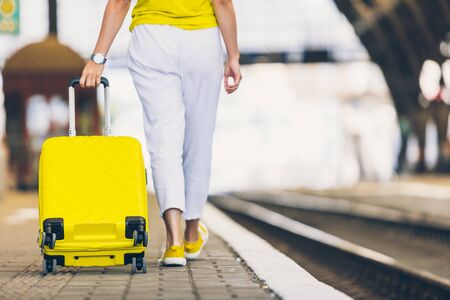woman with yellow bag at railway station copy space