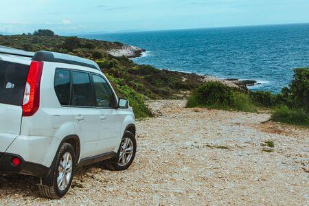 white suv car at rocky beach near sea. car travel concept. background