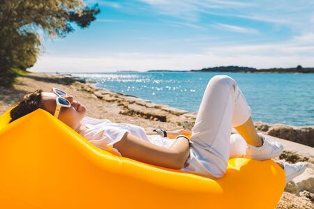 woman resting at yellow inflatable air sofa at the sea beach in sunny day. summer vacation