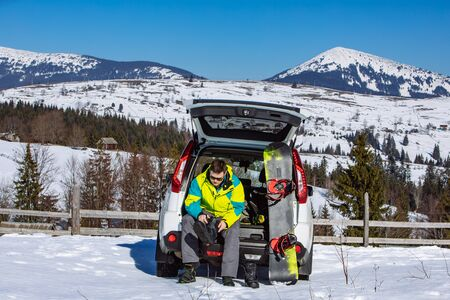 man sitting in car trunk changing for snowboard. mountains on background Фото со стока