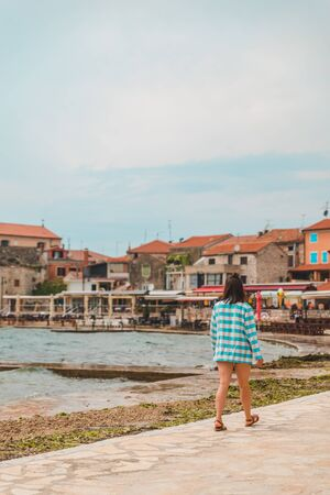 woman walking by umag city quay at stormy weather. copy space. summer vacation