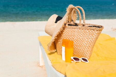 sun protection cream lotion on sun lounger with straw bag and hat. summer vacation. Фото со стока