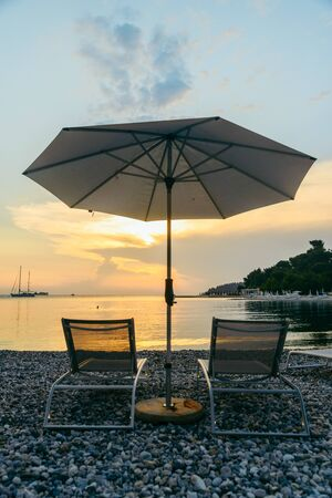 view of sea beach with sun loungers and umbrellas. copy space Фото со стока