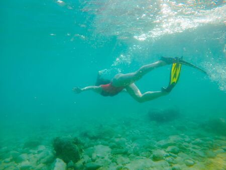 woman in red swimming suit underwater with snorkeling mask and flippers summer vacation Banque d'images - 149580247