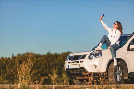 woman near white suv car enjoying sunset road trip concept blue sky on background