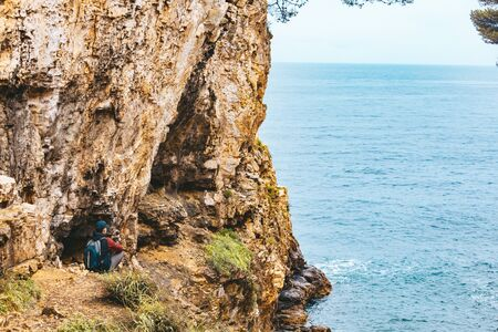 man with backpack at edge of the cliff looking at sea. copy space