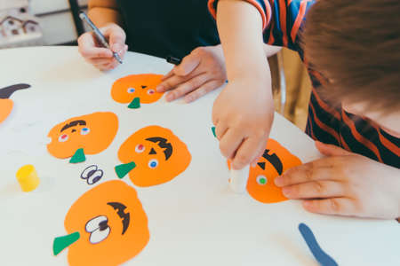 young mother with toddler son making craft pumpkins for halloween holiday family time