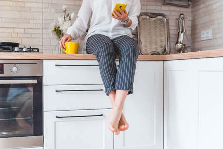 woman sitting on kitchen table with phone and yellow mug. drinking tea