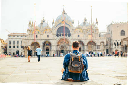 young man sitting on the ground looking at cathedral saint marco basilica copy space. travel concept