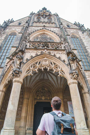 tourist man with backpack looking at old gothic church copy space