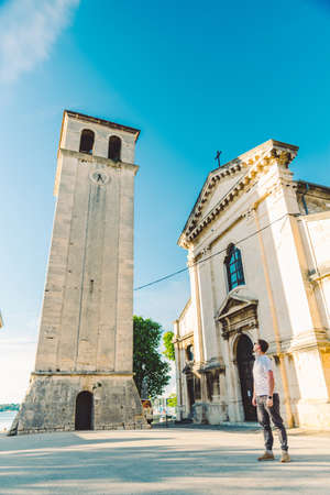 man standing at square looking at old roman cathedral church in pula city. tourism concept