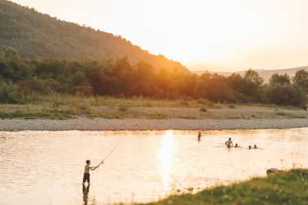 view of sunset in mountains above people swimming in river. summer time. Reklamní fotografie
