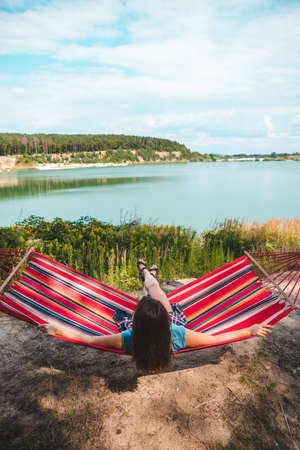 woman laying on hammock enjoying the view of summer lake copy space Banque d'images