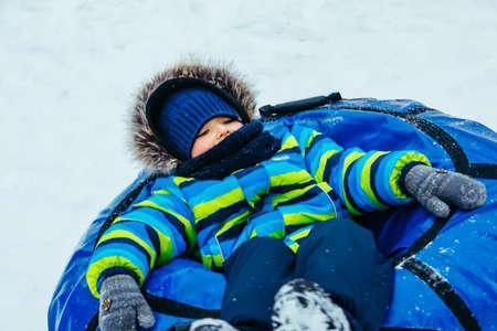 little kid in snow tube. winter time activities Reklamní fotografie