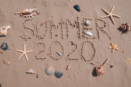 summer 2020 text on sand beach shells and starfish around. overhead