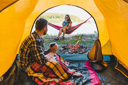 couple resting near fire. man sitting in tent woman laying on hammock. camping concept