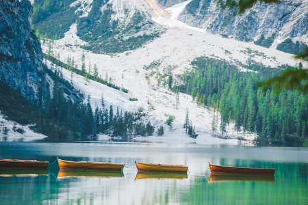 boats at the middle of braies lake in Italy. summer vacation. mirror reflection of mountains in water 免版税图像