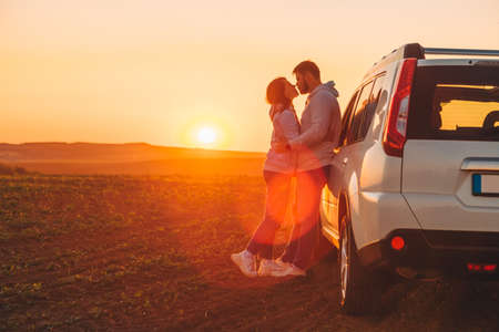 romantic moment couple kissing on sunset near white suv car copy space.