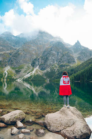 young woman covered with poland flag looking at lake in tatra mountains in carpathian