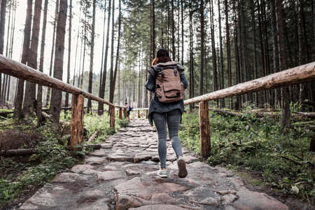 woman hiker walking by stone trail in forest with backpack Banque d'images