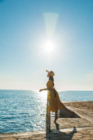 young pretty woman in yellow sundress at sea beach at sunset
