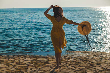 young pretty smiling woman in yellow sundress walking by stone beach. summer vacation concept