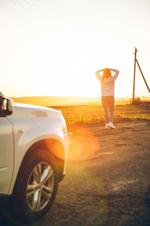 woman enjoying of sunset ar countryside. standing near white SUV. road trip Stock Photo