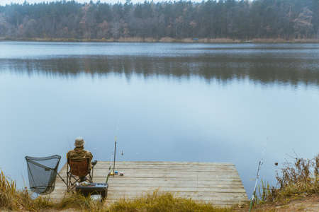 fisherman fishing at calm autumn lake copy space Reklamní fotografie
