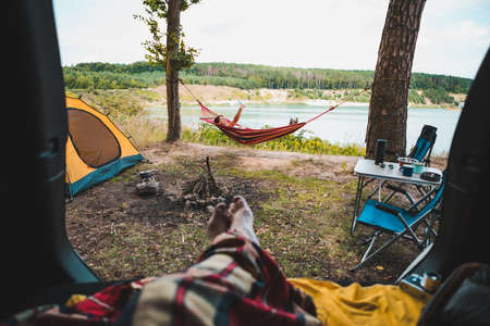 person view couple resting at camping woman laying in hammock with beautiful view of forest lake hiking concept