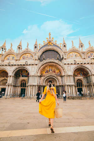 woman in yellow sundress with straw hat walking to saint mark basilica venice italy Stock fotó
