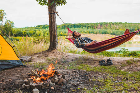man laying on hammock at lake beach near camp fire tourism concept