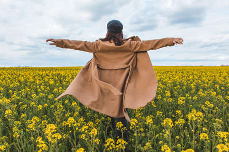 young pretty smiling woman walking in yellow rapeseed field. copy space