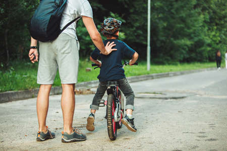 father teaching son how to ride bicycle. summer time. public park