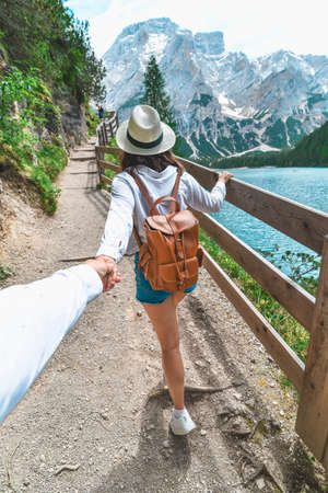 follow me concept woman walking by trail around lake in mountains. copy space