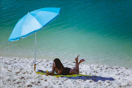 woman in swimsuit walking by sand beach blue sun umbrella and yellow blanket summer vacation